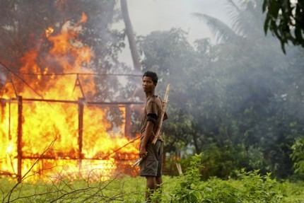 An ethnic Rakhine man holds homemade weapons as he stands in front of a house that was burnt during  fighting between Buddhist Rakhine and Muslim Rohingya  communities in Sittwe